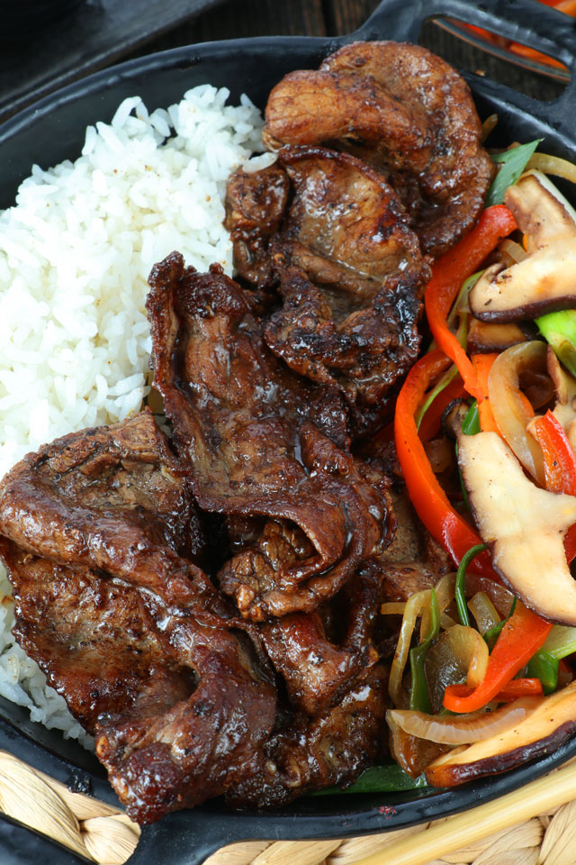Cooked thin cuts of beef sirloin with rice and vegetables on side.