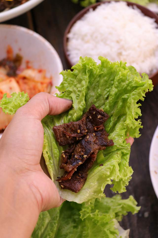 Bulgogi wrap in lettuce leaf with kimchi and rice