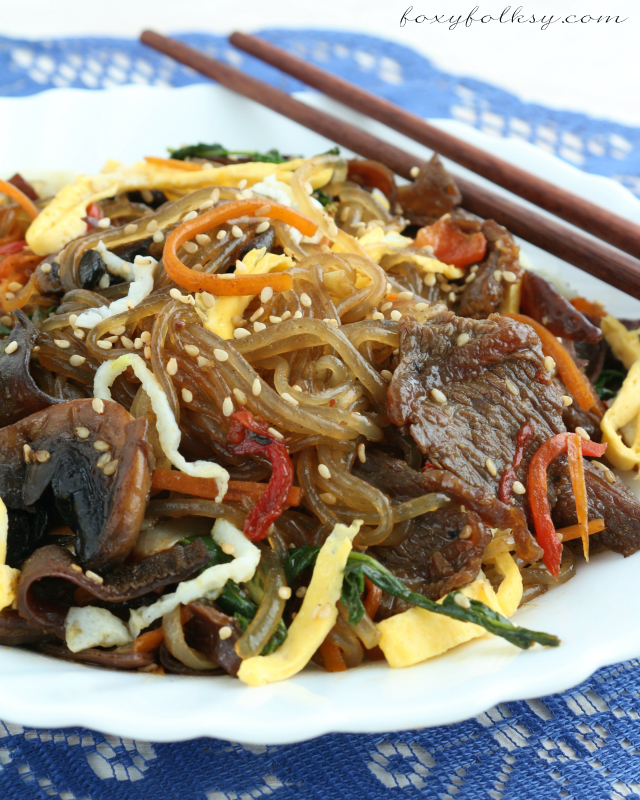 Try this easy Japchae recipe, a popular Korean dish of sweet potato noodle, stir-fried in sesame oil with vegetables, meat and sweet-savory sauce.| www.foxyfolksy.com