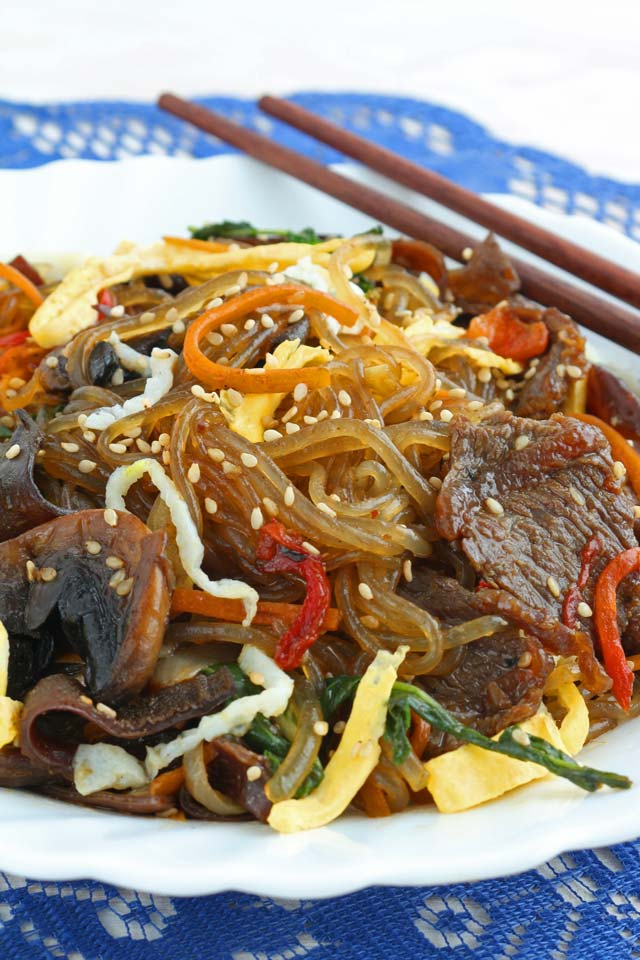 Japchae served on a plate with chopstick