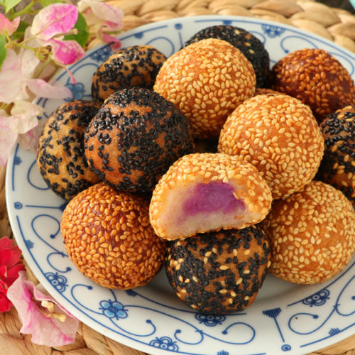 Fried glutinous rice balls with filling covered in sesame seeds