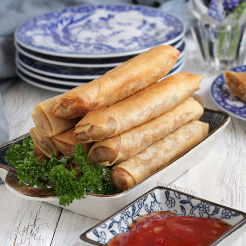 Fried tuna spring rolls served on a plate with dip.