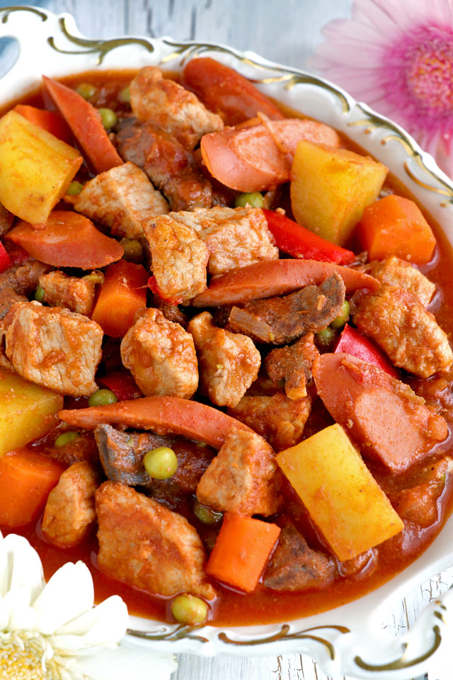 Filipino tomato-based pork stew with meat, liver, potatoes, carrots, hotdogs, and green peas