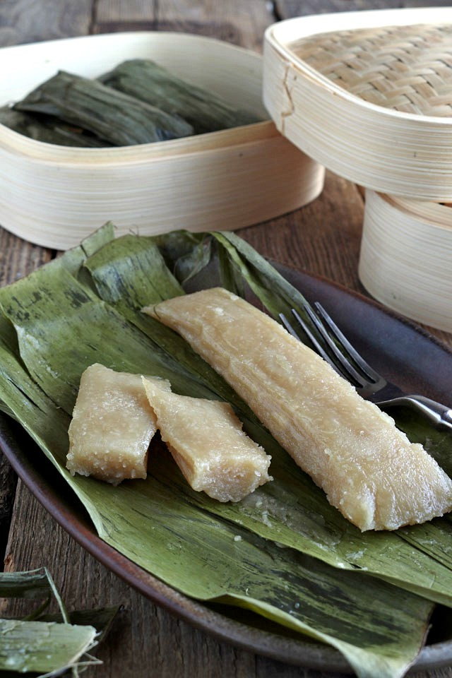 Cassava Suman is a Filipino delicacy of steaming a mixture of grated cassava, coconut milk, and sugar in banana leaves. Try this great Cassava recipe now! | www.foxyfolksy.com