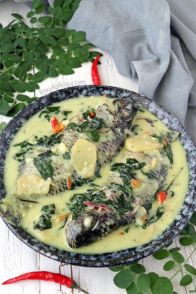 Try this creamy and spicy, Ginataang Tilapia (Tilapia in coconut milk) recipe. All done in less than 15 minutes! | www.foxyfolksy.com