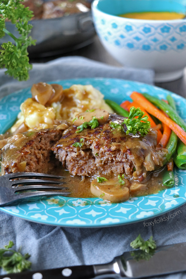Try this simple Salisbury Steak recipe complete with Mushroom Gravy! So tender and juicy Steak patties swimming in thick tasty gravy! | www.foxyfolksy.com