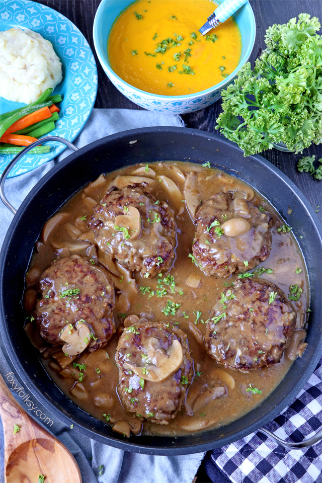 Try this simple Salisbury Steak recipe complete with Mushroom Gravy! So tender and juicy Steak patties swimming in thick tasty gravy! | www.foxyfolksy.com