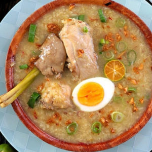 Filipino Arroz Caldo from glutinous rice, chicken, ginger, lemongrass with hard-boiled egg and brown garlic toppings