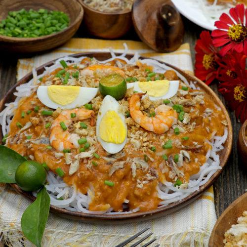 Pancit Luglug with hard-boiled eggs, shrimp, pork rind, and shredded smoked fish