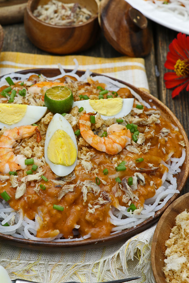 Pancit Luglug using thick cornstarch noodles with orange savory sauce and toppings