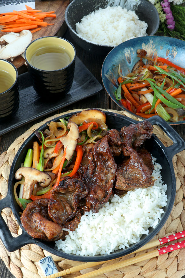 Grilled beef slices serve on a bowl with stir-fried vegetables and rice.