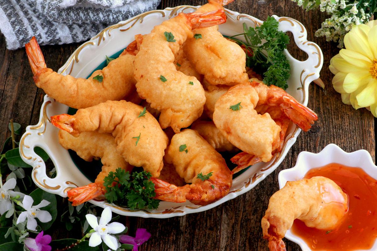 A plate full of fried battered shrimp.