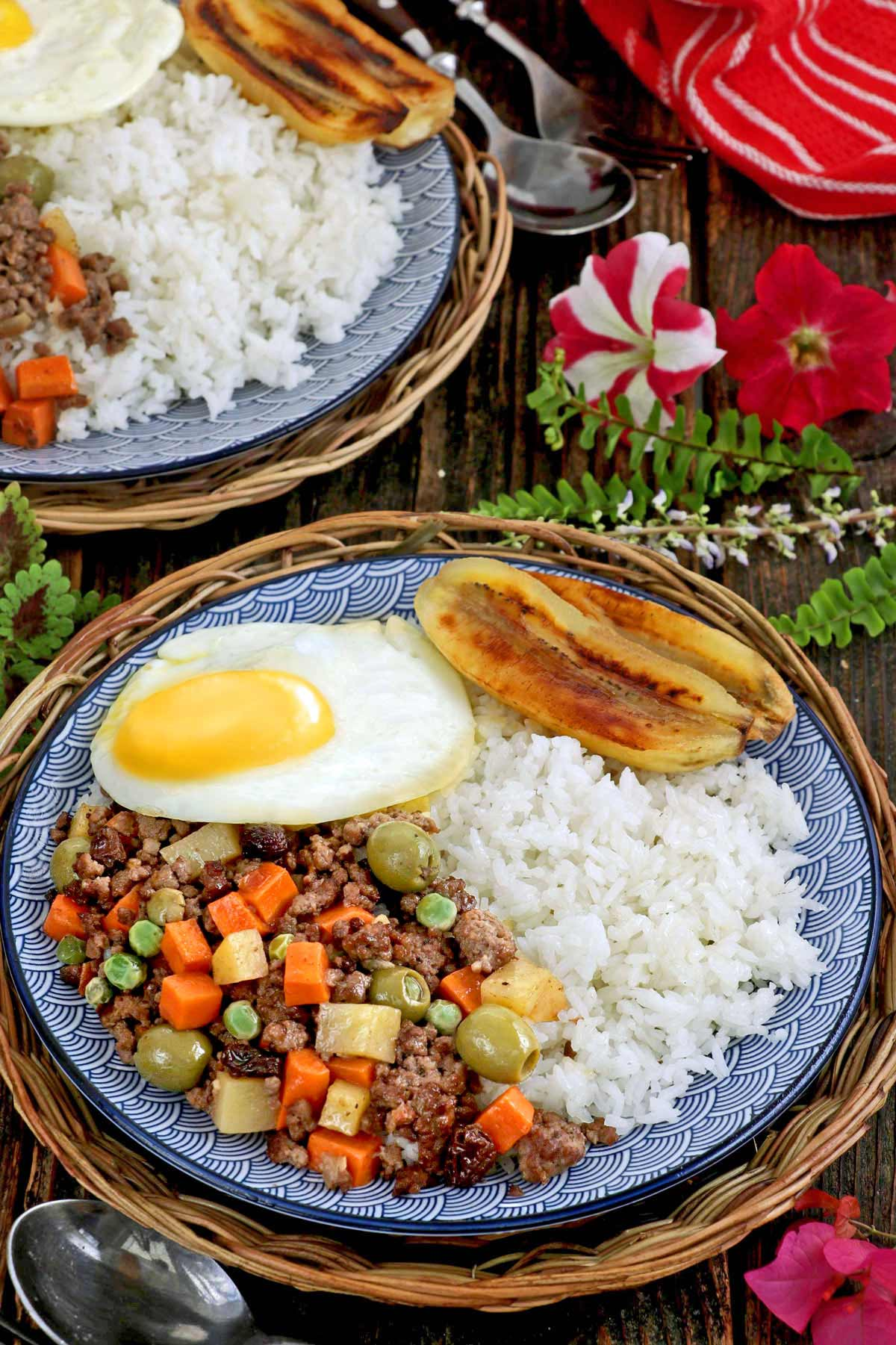 A plate of rice with cooked ground meat, fried egg and fried banana.