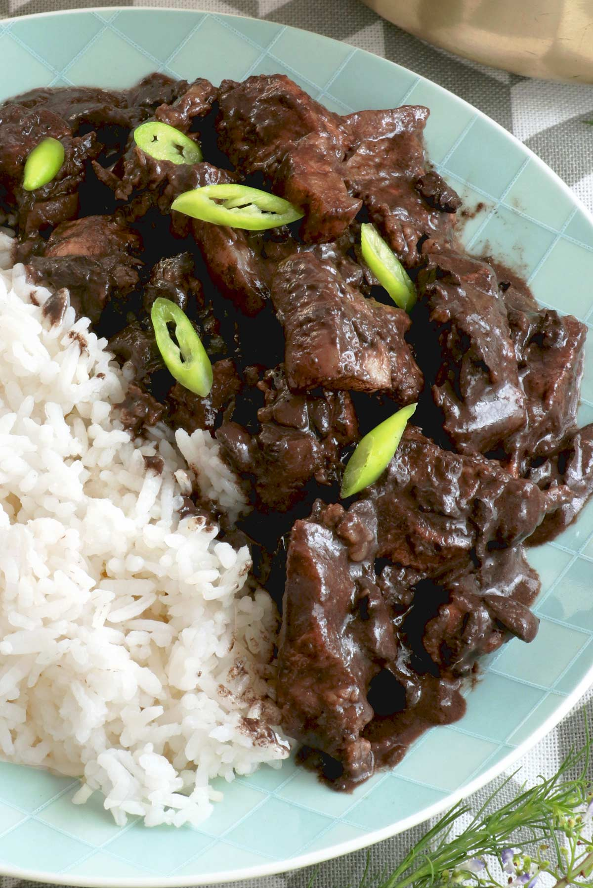 Dinuguan with rice on a plate.