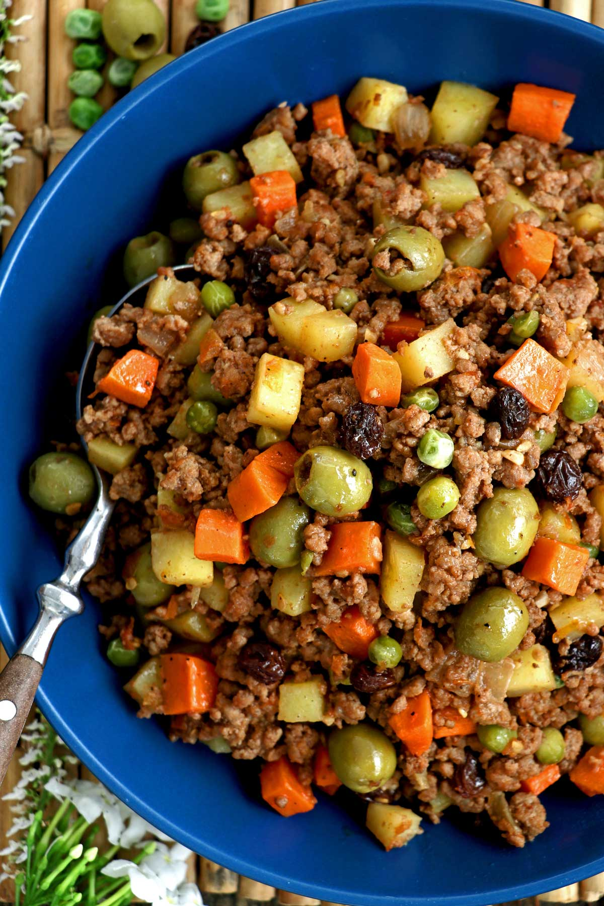 Picadillo recipe complete with ground beef, potatoes, carrots, olives, green peas, and raisins cooked in fresh tomatoes.