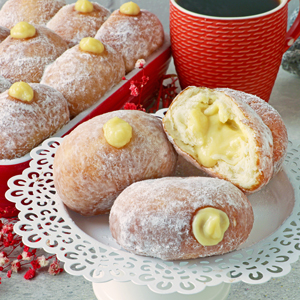 Vanilla pastry cream-filled doughnuts on a plate.