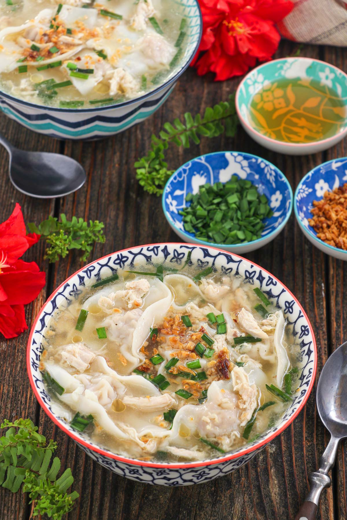 Bowls of warm pancit molo with green onions and toasted garlic.